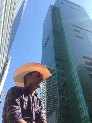 Justin Moore profile against tall glass skyscraper
